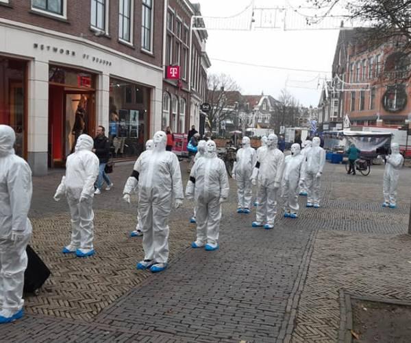 Mysterieuze figuren in wit demonstreren op het Schaapmarktplein van Sneek
