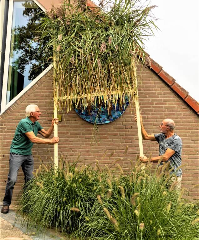 Vrijwilligers Ruurd Abma en Harry de Vries onthullen het door leerlingen van Klaver Fjouwer gemaskte wapen van Oudega als tableau aan de gevel van het vernieuwde Joo