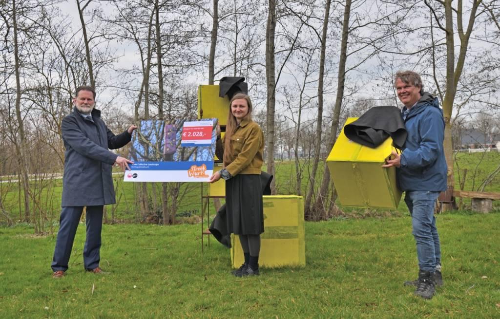 Gedeputeerde Klaas Fokkinga overhandigt de cheque van 2028 euro aan Henk Pilat en Monika Balu, initiatiefnemers van het Slow Collective Landscape project