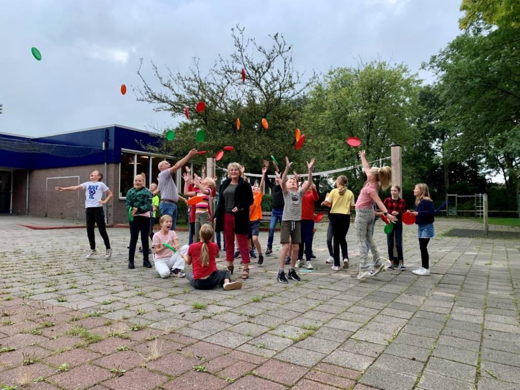 Wethouder Mirjam Bakker deelt frisbees uit aan de leerlingen van groep 7/8 van CBS it Harspit in Oppenhuizen.