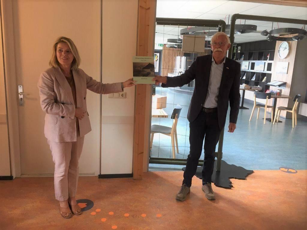 Oud-burgemeester van Wymbritseradiel, Jacob Reitsma biedt het boek aan